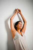 Pregnant Hispanic woman, hands over head, leaning against white wall