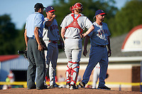 Auburn Doubledays pitching coach Tim Redding (17) turns towards the dugout after talking with relief pitcher Kevin Mooney (33) and catcher Erik VanMeetren (8), with umpire Emil Jimenez to the left, during the second game of a doubleheader against the Batavia Muckdogs on September 4, 2016 at Dwyer Stadium in Batavia, New York.  Batavia defeated Auburn 6-5. (Mike Janes/Four Seam Images)