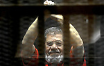 FILE PHOTO: Egypt's ousted Islamist president Mohamed Morsi, wearing a red uniform, looks on from behind the defendant's bars during his trial on espionage charges at a court in Cairo on June 18, 2016. Former President Mohamed Morsi died on Monday in court after the conclusion of a trial session in the espionage lawsuit, Egyptian state TV said. Photo by Stringer