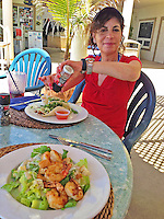 9 July 2013: SCUBA diver Sally Herschorn enjoys lunch on the oceanside deck at Cobalt Coast Resort, in West Bay, Grand Cayman Island. Located in the British West Indies in the  Caribbean, the Cayman Islands are renowned for excellent scuba diving, snorkeling, beaches and banking.  Mandatory Credit: Ed Wolfstein Photo