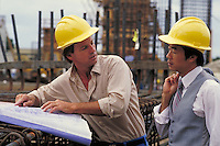 Asian and American businessmen wearing hardhats at a construction site. occupations, communication. Jim Creed, Harold Sue. Colorado.
