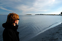 Woman with red hair standing on a sandy beach and wearing black sunglasses looking Pacific Ocean, Victoria City, East Pacific ocean, south of Vancouver Island, British Columbia, Canada, North America (MR)