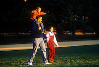 Son and daughter walk with dad in the park.