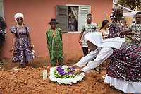 Nigeria. Enugu State. Agbani. Igbo funeral ceremony of Mrs Ann Mary Azuka Nbubuisi Anike who passed away at 72 years old. The burial takes place in the family home's garden. A religious nun covers the grave with a wreath of flowers. Some women in the assistance wear a head tie which is a women's cloth head scarf. The head tie is used as an ornamental head covering or fashion accessory. Its use or meaning can vary depending on the country and/or religion of those who wear it. The head tie is called gele in Nigeria.11.07.19 © 2019 Didier Ruef
