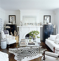 In the living room two framed reptilian prints are displayed above a matching pair of lacquered cupboards whilst a large zebra-skin covers the oak floorboards