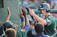 First baseman Chris McGuiness (24) of the Greenville Drive high-fives teammates after scoring a run a game against the Lexington Legends April 25, 2010, at Fluor Field at the West End in Greenville, S.C. Photo by: Tom Priddy/Four Seam Images