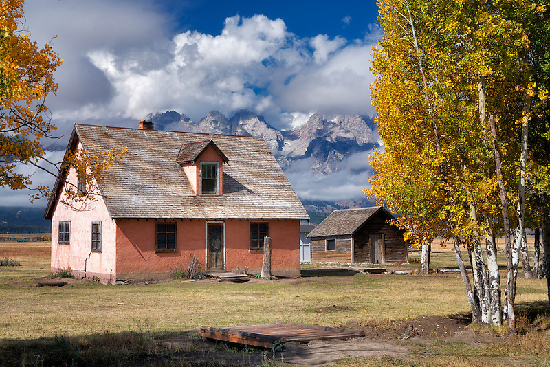Pink House at John Moulton Homestead with Teton Mountains and clearing clouds. Teton National Park, Wyoming