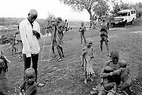 """Ethiopia. South Omo Zone. Salamago district. Omo river. Mursi tribe. People waiting for the start by the non-governmental organization (NGO) Médecins Sans Frontières (MSF) Switzerland of vaccination injections against tetanos, dpt, bcg and measle. MSF Switzerland as part of its health project inoculate children. The Mursi tribe is an Agro-pastoralist group. Nomadic. Mursi women are known as """"disk-lip"""" women.The bottom lip is slit along its full length and the front bottom row of teeth are pulled out to accomodate the ceramic disk  which is handmade with a rim around which the stretched lip is pulled. The disk is seen as a symbol of beauty and wealth, and often the younger girls will pierce and strech their ear-lobes, inserting a matching disk in the extended lobe. The Mursi tribe is located in the Debub Omo Zone (South Omo Zone) of the Southern Nations, Nationalities and Peoples's région. © 2001 Didier Ruef"""