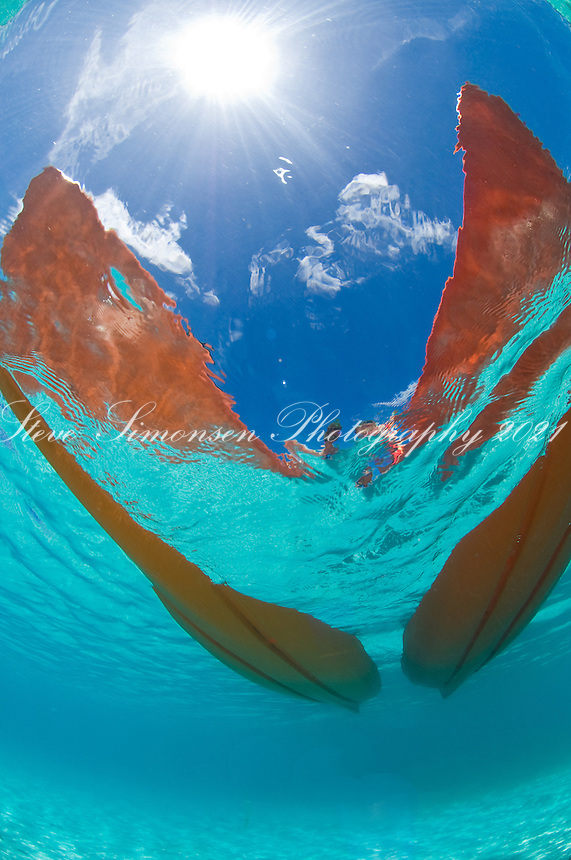 Looking up through clear water at two kayaks.St John, US Virgin Islands