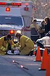 EMTs attending to badly injured victim of car crash on road as concerned eyewitnesses watch, ambulance