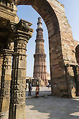 Delhi, India. The Qutub Minar tower viewed throughan arch from the Quwwat-ul-Islam mosque