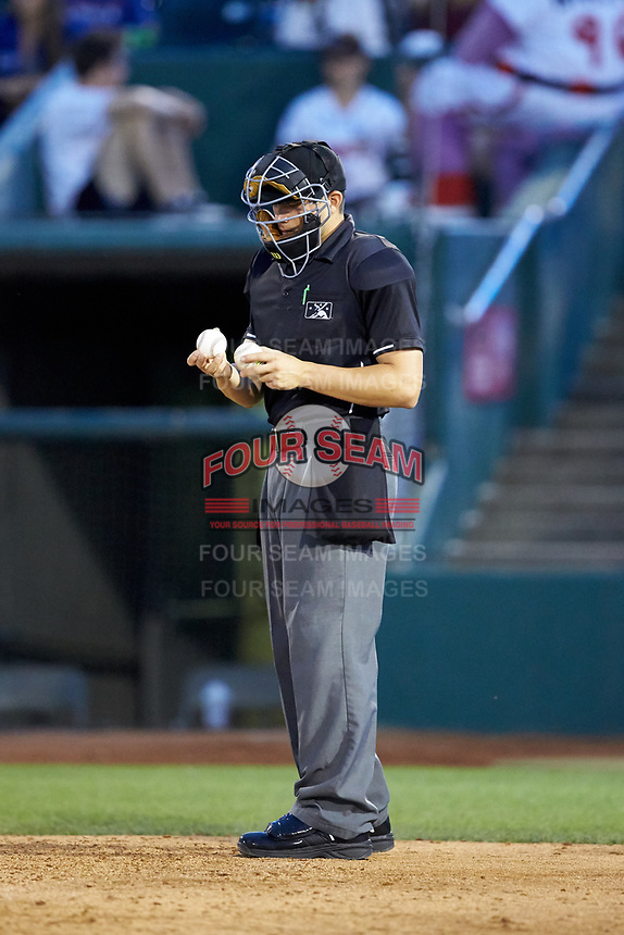 Home plate umpire Steven Hodgins checks the baseballs during the Midwest League game between the South Bend Cubs and the Lansing Lugnuts at Cooley Law School Stadium on June 15, 2018 in Lansing, Michigan. The Lugnuts defeated the Cubs 6-4.  (Brian Westerholt/Four Seam Images)