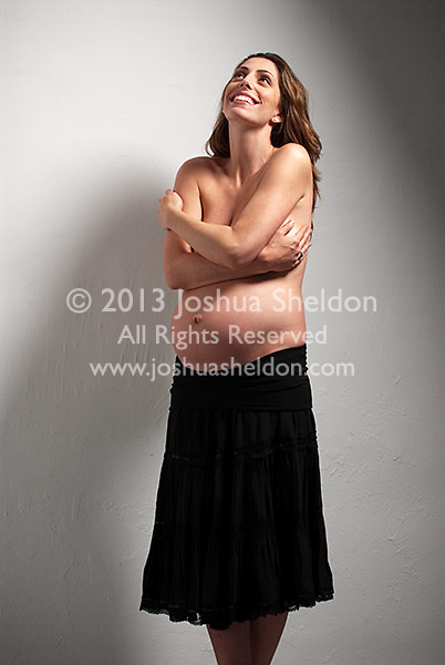 Smiling topless pregnant Caucasian woman, standing up, arms over breasts