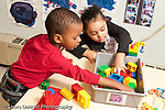 Education preschool 3-4 year olds boy and girl reaching into plastic bin to grab colorful connecting plastic construciton pieces (Duplo) horizontal