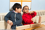 Education preschool 4 year olds two boys playing together in block area pretending to