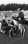 Picnic at polo match Windsor Great Park, the car park. Berkshire England. Circa 1985. Wealthy upper class style, the woman is wearing a Hermes headscarf and blue Burberry waxed jacket as is he, plus a flat tweed cap. She's on a Bucks Fizz but made with Henkell Trocken a German sparkling white wine. Their car is a convertible Porsche 911 SC Cabriolet.