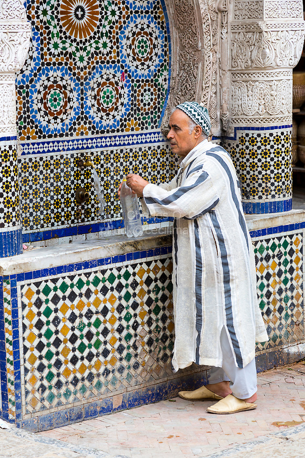 Fes, Morocco.  Place Nejjarine.  Man Filling His Water Bottle  at the Public Fountain.