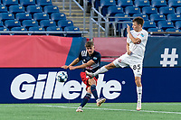 FOXBOROUGH, MA - JULY 9: Justin Rennicks #12 of New England Revolution II clears the ball as Antonio Carlini #85 of Toronto FC II defends during a game between Toronto FC II and New England Revolution II at Gillette Stadium on July 9, 2021 in Foxborough, Massachusetts.