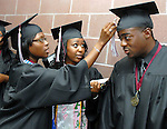 Monique Smith adjust the tassel of fellow graduate Jerald Flowers while Tiara Mays looks on before the Texas Southern University commencement Saturday May 16,2009.(Dave Rossman/For the Chronicle)