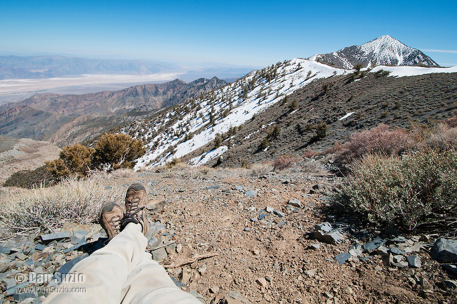 A hiker on the Telescope Peak Trail takes a break to enjoy the view of Death Valley and Telescope Peak.  The Badwater area of Death Valley, 282 feet (86 meters) below sea level, is in the left background. On the right is Telescope Peak, elevation 11,049 feet (3,368 meters). Death Valley National Park, California.