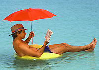Floating, relaxing and reading in the water, with a red umbrella