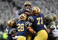 PHILADELPHIA, PA - DEC 14, 2019: Navy Midshipmen quarterback Malcolm Perry (10) is lifted off the ground and carried backward for a loss during game between Army and Navy at Lincoln Financial Field in Philadelphia, PA. The Midshipmen defeated Army 31-7. (Photo by Phil Peters/Media Images International)