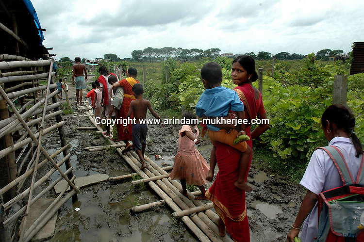 Indian slum dwellers crossing a mud pool at Nonadanga in Kolkata which is supposed to be the road to enter their temporary huts. Nonadanga is the the place given by the Governmnet as the temporary shelter for the evacuated families from the slums of Kolkata, India  Arindam Mukherjee