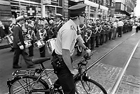 Switzerland. Geneva. Town Center. A policeman on a bicycle. A groups of boys belonging to a fanfare gets ready to play in the streets on Music Day. A fanfare is a short musical flourish that is typically played by various brass instruments, often accompanied by percussion. A marching band is a group in which instrumental musicians perform while marching often for entertainment. The Fête de la Musique, also known in English as Music Day, Make Music Day or World Music Day, is an annual music celebration that takes place on 21 June ( but usually during the previous or following weekend). On Music Day the citizens of a city or country are allowed and urged to play music outside in their neighborhoods or in public spaces and parks. Free concerts are also organized, where musicians play for fun and not for payment. 22.06.1993 © 1993 Didier Ruef