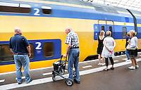 Nederland Amsterdam. Mensen wachten op de trein op Centraal Station
