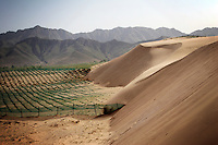 Sand dunes move onto farmland in Hebei Province, China. Desertification is the process by which fertile land becomes desert, typically as a result of drought, deforestation, or inappropriate agriculture. 41 % of China's landmass in classified as arid or desert. Inappropriate farming methods and over cultivation have contributed to the spreading of deserts in China in recent years.