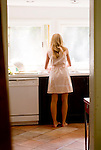 Woman standing in kitchen with back to camera