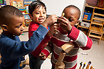 Education Preschool 4 year olds group of three boys pretend play with human figures on top of block tower construction
