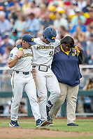 Michigan Wolverines designated hitter Jordan Nwogu (42) is helped off the field by head coach Erik Bakich (23) and team trainer Kimberly Hill after being injured against the Vanderbilt Commodores during Game 2 of the NCAA College World Series Finals on June 25, 2019 at TD Ameritrade Park in Omaha, Nebraska. Vanderbilt defeated Michigan 4-1. (Andrew Woolley/Four Seam Images)
