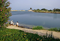 Carthage, Tunisia.  Punic Ports, now resembling small lakes bordered by luxurious homes, date from the 4th. Century B.C.  This was the naval, or military, port.  A commercial port is adjacent.  Men Fishing.