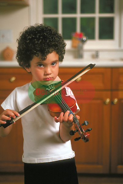 young boy playing violin in kitchen