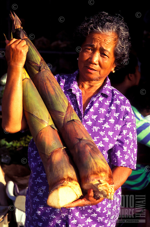 Vendor holding fresh bamboo shoots at the Hilo Open Market