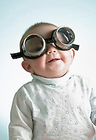 Portrait of 6 month old laughing baby girl wearing welders goggles over eye