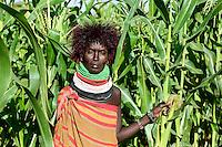 KENYA Turkana, Lodwar, Turkana village Kaitese, Turkana woman with wig infront of maize field, traditional the Turkanas a cattle holder but due to climate change the shift to farming too / KENIA Turkana, Lodwar, Dorf Kaitese, Turkana, eigentlich traditionell Viehhalter, beginnen mit Unterstuetzung von GIZ und Save the children ein Maisanbau Projekt zur Ernährungssicherung und Anpassung an den Klimawandel, Frau mit Peruecke