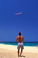 Man playing with a remote control glider on the beach
