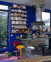 A series of colourful stools at the breakfast bar and a collection of plates displayed on the deep blue walls delineate the open-plan kitchen