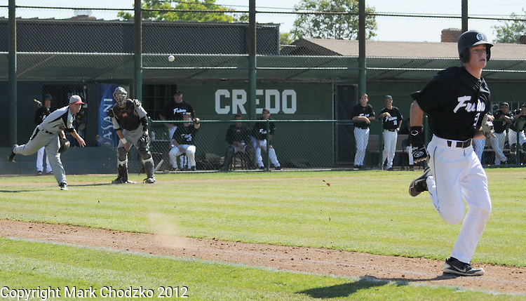 Runner tries to beat throw to first base as the catcher looks on.