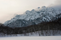 Evening falls over the rugged peak of Togakushi Mountain from Kagami-ike Lake in winter, Nagano, Japan.<br /> <br /> (title translation Daniel Crump Buchanan)