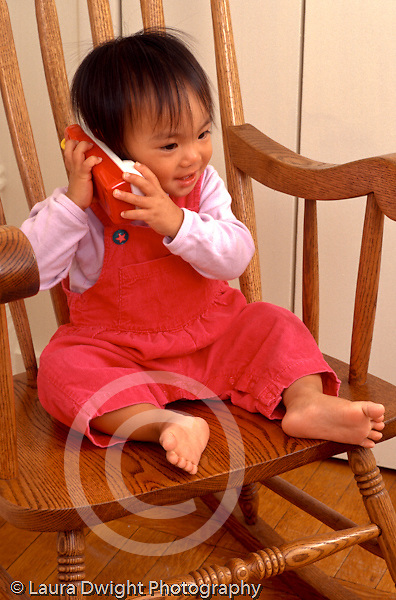 15 month old toddler girl sitting in rocker pretend play talking on toy telephone vertical