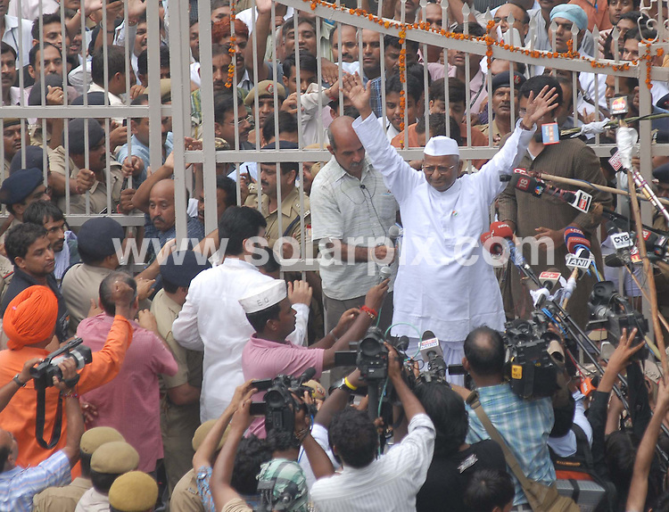 """**ALL ROUND PICTURES FROM SOLARPIX.COM**                                             **WORLDWIDE SYNDICATION RIGHTS**                                                                                  Caption: Anna Hazare at a rally in New Dehli after his release from the prison -  India's most prominent anti-corruption crusader emerged from a New Delhi jail today to the wild cheers of Long live Mother India as he prepared to embark on a 15-day public hunger strike. .Emerging from Delhi's Tihar Jail Mr. Hazare was greeted by huge cheers from the large crowd gathered at the prison gate. """"Whether I live or not,"""" he told supporters in a short address, """"corruption should not live.""""   .After three days in jail, anti-corruption crusader Anna Hazare reached New Delhi's Ramlila Ground and addressed thousands of supporters urging them to continue the fight for a strong anti graft bill called Lokpal Bill..In a massive show of support, thousands of people lined up Delhi street where civil society leader Anna Hazare made his way to the Ramlila Ground to hold his indefinite fast for a strong watchdog for anti graft cases..On the way to venue to continue his fast he visited India's father of nation Mahatama Gandhi's mausoleum Rajghat to pay respects to Mahatma Gandhi ahead of his protest fast at Ramlila Ground. .Just past the Tihar prison gates he addressed the crowd outside , raising his hand to the air and shouting """"Victory to Mother India"""" and declaring the fight against corruption would continue whether he was """"alive or not"""" before slowly winding his way in a truck decorated with flags through massive crowds..His movement has created a frenzy amongst India's hundreds of relentless news broadcasters and brief speech after emerging from prison was carried live across India on the country's many all-news channels, and Mr Hazare clearly had a flair for such a media moment. New Dehli, India. 19 August 2011                                                                         This"""