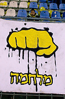 """A Betar Jerusalem Hebrew sign with the word """"Milchama"""" - """"War""""  is seen during the match for the league against Hapoel Tel Aviv in the Jerusalem stadium """"Tedy"""". Hapel Tel Aviv is considered by Betar fans  the worst enemy in the league which represents the Ashkenazy (European born) lefty club.  Beitar won the match 2 -1. Beitar Jerusalem FC was founded in the 1930's by the right-wing Revisionist Zionist movement, which later formed the Israeli Likud political party, during the British Mandate rule over Palestine. The chanting of the club is racist and mainly against Arabs. The team is the only one in the Israeli league to have never had an Arab player. Beitar is seen as the right wing and Mizrahi (Jews who came from Asia and Africa) club. Photo by Quique Kierszenbaum"""