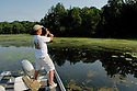 00416-027.06 Fishing (DIGITAL) Angler is casting from boat along a weedy secluded shoreline.  Action, bass, lake, river.  H3R1