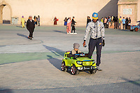 Essaouira, Morocco.  Boy Riding in Toy Car in the Place Moulay Hassan.