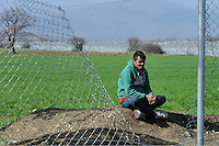 Pictured: A migrant man sits on the soil Tuesday 01 March 2016<br />
