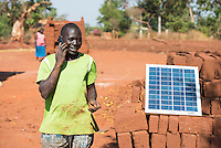 MALAWI, farmer charges his mobile phone with solar panel in village / MALAWI, Bauer Charles Zimba laedt seine Batterie fuer das Mobiltelefon mit einem Solar Panel