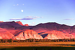 Landscape with full moon and setting sun over Big Flat.  The Salmon River runs along the base of the Lost River Range mountains through stark yet beautiful terrain.  Idaho.